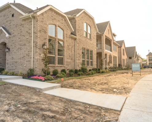 Row of newly built detached single-family homes and sold out sign. Medium size multiple lot properties in new-established community, construction zone with unfinished landscape Irving, Texas, USA